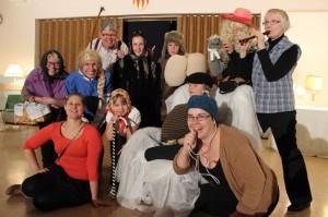 Yhteisöteatterin esittäjät valitsivat kuvaan oman lempiroolinsa asusteet. Iiris Saarikko (71) näytteli muun muassa mummoa, Tiina Vuorisalo (49) suunnistajaa, Hannu Kotilainen (62) viikinkiä, Ronja Saario (8) ja Piia Virtanen (37) mummoa, Iida Virtanen (12) viikinkiä, Aleksi Saario (12) maanrakentajaa, Mikko Madetoja (12) baarikärpästä, Mari Saario (38) suunnistuskisan vetäjää. Muusikkona toimi Päivi Korvensyrjä. Edessä istuu ohjaaja Suvi Kanniainen. Timo Vuorisalo puuttuu kuvasta.