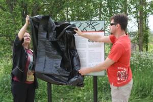 Kaarinan suunnitteluhortonomi Sirkka Laitinen sekä aluemestari ja puiston töitä johtanut Matias Rikikoski kuorivat jätesäkkien alta tuoreen opastaulun, jossa kerrotaan alueen muinaisjäännöksistä.