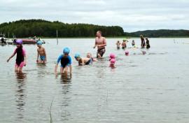 Nuorimmat uimakoululaiset uivat käsipohjaa kohti rantaa.