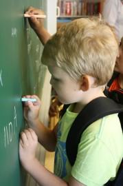 Ekaluokkalaiset saivat kirjoittaa Rungon koulussa taululle oman nimensä.