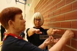 Tasapaino-työpajan aluksi Leena Korvenniemi ja Marja-Leena Saari Sauvosta testasivat omaa tasapainoaan. Kumpikin seisoi vuorollaan seinän vierellä, kädet edessä 90 asteen kulmassa. Sitten kurkotettiin suoraan eteenpäin. Toinen heistä mittasi, kuinka pitkälle kädet ylsivät. Kumpikin sai reippaasti yli parhaimman tason.