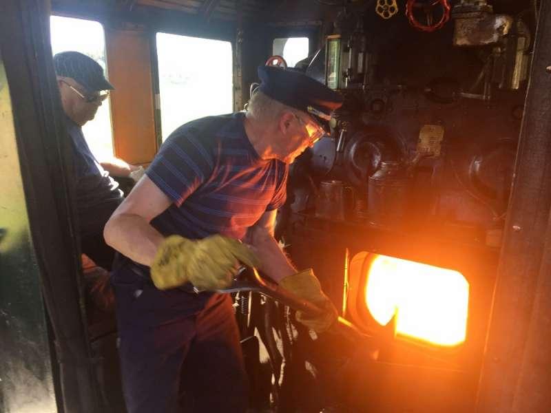 Pekka Hupponen lapioi hiiltä. Junan omistaja, Reijo Sarantila seuraa ratamerkkejä.
